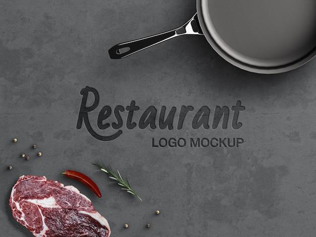 Maquete do logotipo da culinária do restaurante conceito de cozinha na superfície de concreto do grunge com utensílios de cozinha isolados