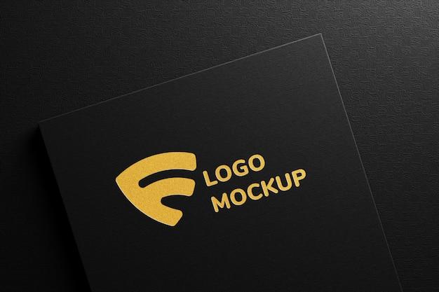 Maquete do logotipo de luxo com folha de ouro em relevo em papel preto