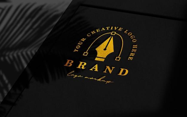 Maquete do logotipo dourado de papéis pretos