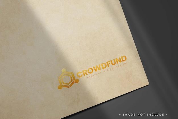 Maquete do logotipo dourado em papel pardo