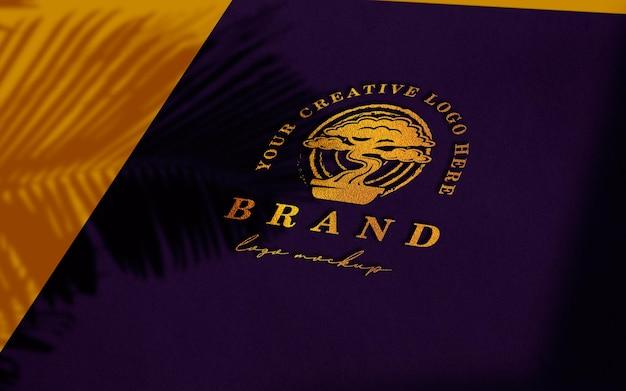 Maquete do logotipo dourado em papel roxo
