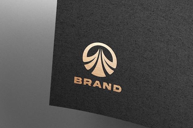 Maquete do logotipo dourado em relevo em papel preto