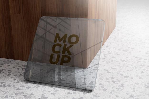 Maquete do logotipo dourado em vidro com fundo de madeira
