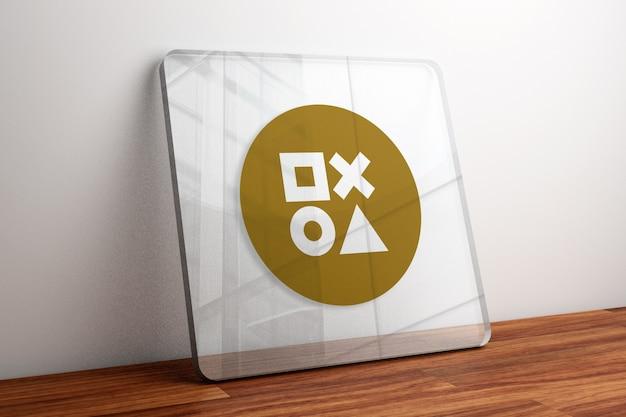 Maquete do logotipo dourado em vidro na mesa de madeira
