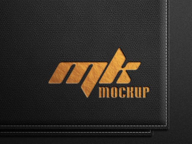 Maquete do logotipo em couro preto com estampa dourada em relevo
