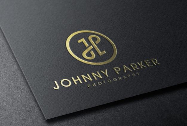 Maquete do logotipo em folha de ouro com relevo no cartão preto