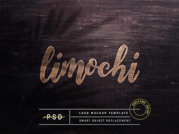 Maquete do logotipo em relevo na madeira marrom escura