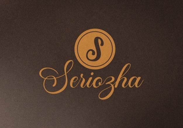 Maquete do logotipo em relevo na textura de tecido marrom