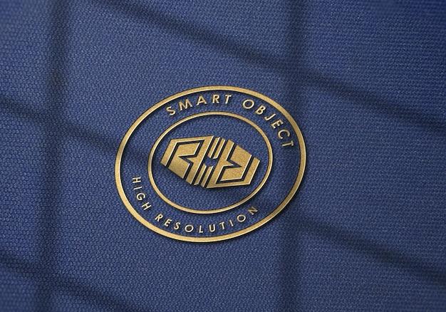 Maquete do logotipo em tecido denim com efeito dourado