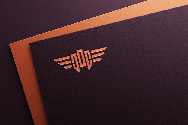 Maquete do logotipo gravado em papel escuro