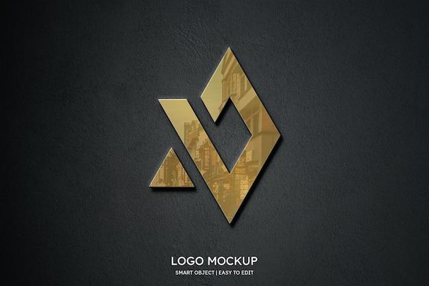 Maquete do logotipo luxuoso e elegante em ouro sobre fundo preto fosco