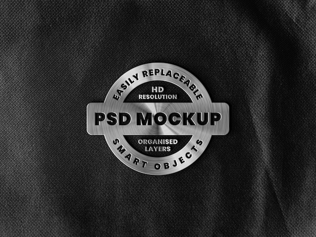 Maquete do logotipo metálico do pincel na superfície áspera preta