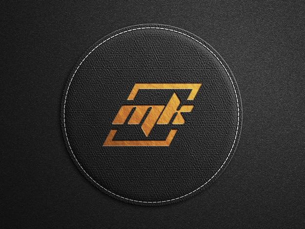Maquete do logotipo na superfície arredondada de couro preto com estampa dourada em relevo