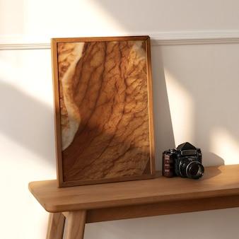 Maquete do porta-retrato em uma mesinha de madeira com uma câmera analógica