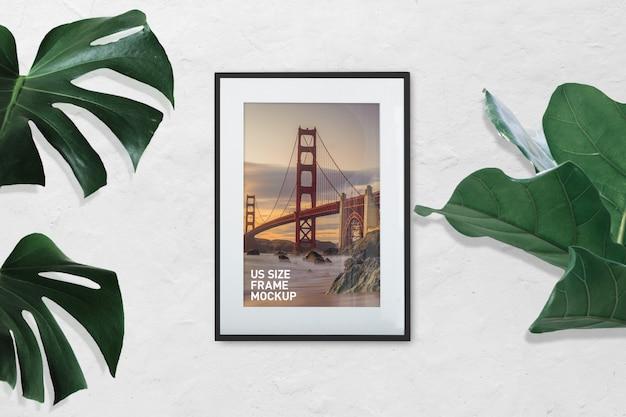 Maquete do quadro foto preto vertical na parede branca com plantas