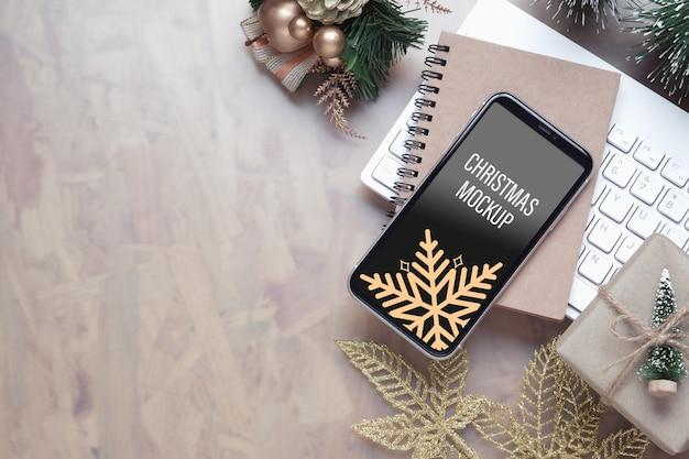 Maquete do smartphone na mesa do escritório em casa para plano de fundo de natal e ano novo