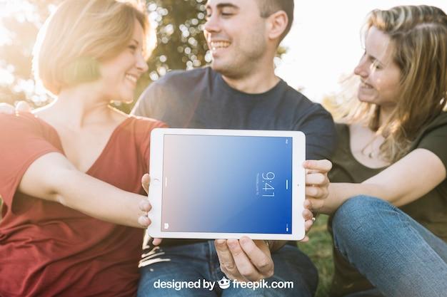Maquete do tablet com amigos ao ar livre
