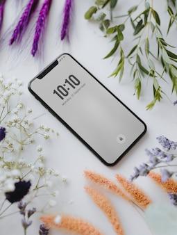 Maquete do telefone emoldurado com um monte de flores coloridas secas