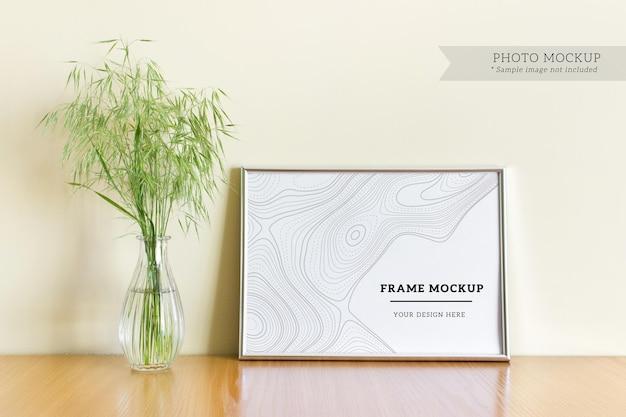 Maquete editável de psd com moldura de prata em branco a4 horizontal com plantas silvestres em um vaso de vidro