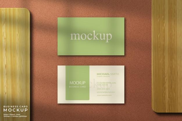 Maquete elegante de cartão de visita com vista superior e fundo de madeira