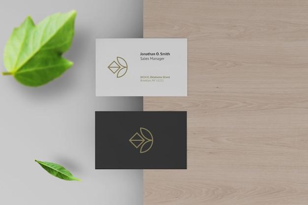Maquete elegante de cartão de visita escuro e branco com folha como fundo