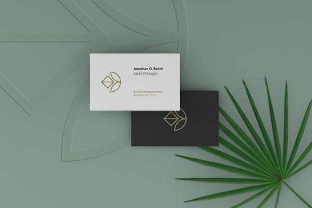 Maquete elegante de cartão de visita escuro e branco com plantas como plano de fundo