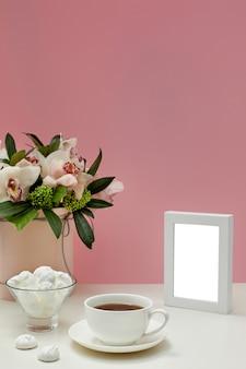 Maquete em branco vista frontal da moldura. flores da orquídea, xícara de chá e doces.
