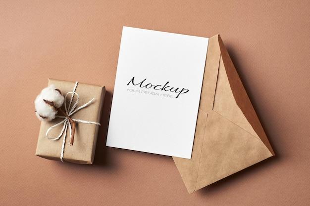 Maquete estacionária de cartão comemorativo com envelope e caixa de presente decorada com flor de algodão