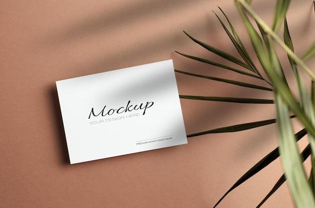 Maquete estacionária de cartão de convite com folha de palmeira de natureza seca