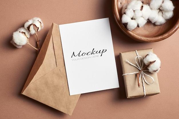 Maquete estacionária de cartão de saudação ou convite com envelope, caixa de presente e decoração de flores de algodão