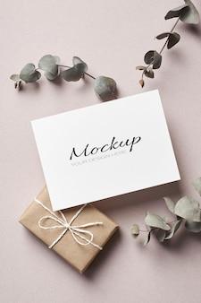 Maquete estacionária de convite ou cartão de felicitações com caixa de presente e galhos de eucalipto seco