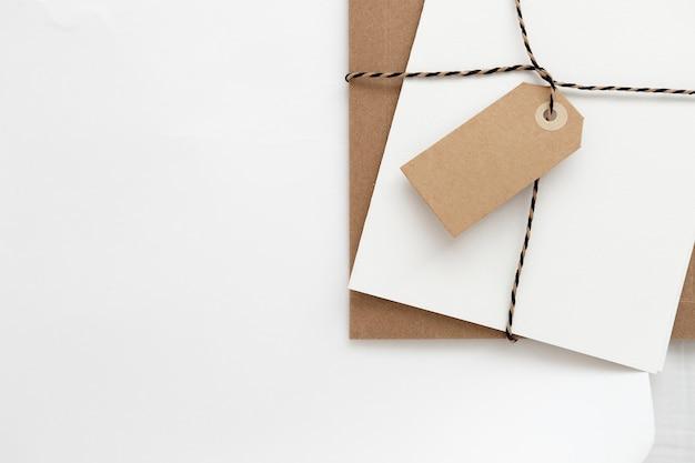 Maquete horizontal minimalista de um papel de embrulho e cartões de papelaria na roupa de cama