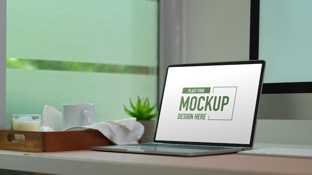 Maquete laptop na mesa do computador com caneca e vela na bandeja de madeira