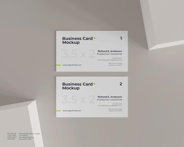 Maquete minimalista de dois cartões de visita brancos com aparência de vista superior