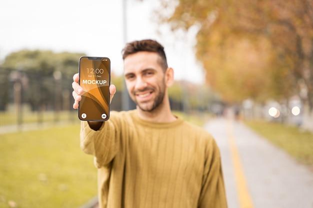 Maquete móvel com retrato masculino segurando o smartphone e olhando para a câmera Psd Premium