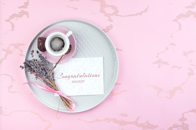 Maquete na nota de papel com uma xícara de café e lavanda seca no prato rosa