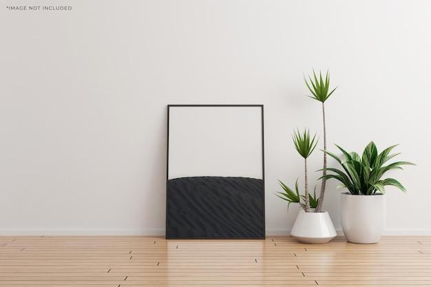 Maquete preta da moldura da foto vertical na parede branca do quarto vazio com plantas no chão de madeira