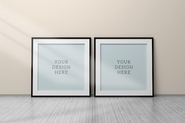 Maquete psd editável com duas molduras em branco quadradas pretas sobre o piso de madeira próximo à parede