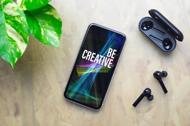 Maquete smartphone com fones de ouvido sem fio e estojo de carregamento na mesa de escritório de trabalho.