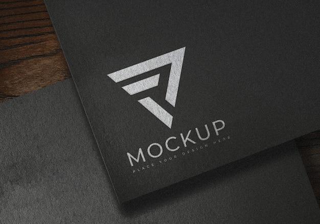 Maquetes de logotipo branco em superfície de textura de papel preto