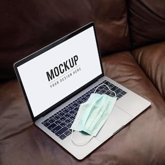 Máscara médica em um laptop com uma tela de maquete