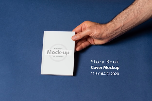 Masculinas mãos segurando um caderno-catálogo fechado com capa em branco