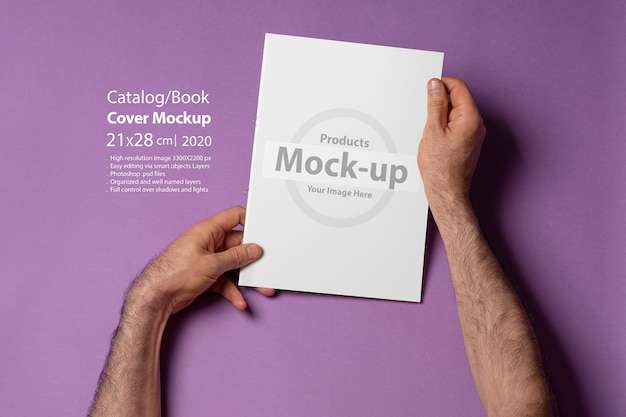 Masculinas mãos segurando um catálogo com capa em branco roxo