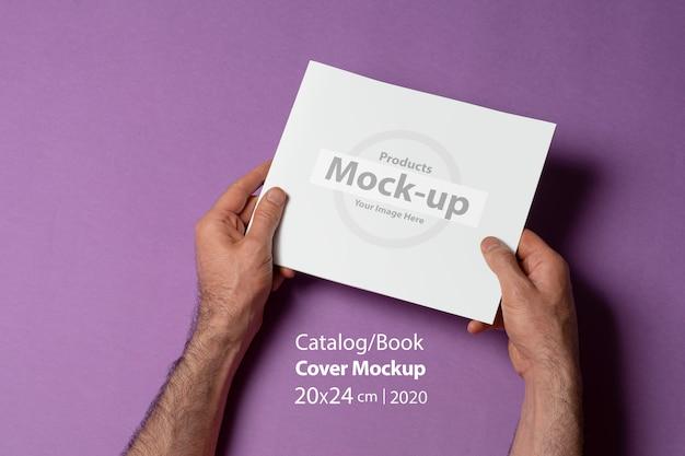 Masculinas mãos segurando um catálogo de proporção quadrada com capa em branco na superfície roxa