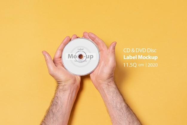 Masculino mão segurando um cd-dvd por duas mãos em frente a parede amarela