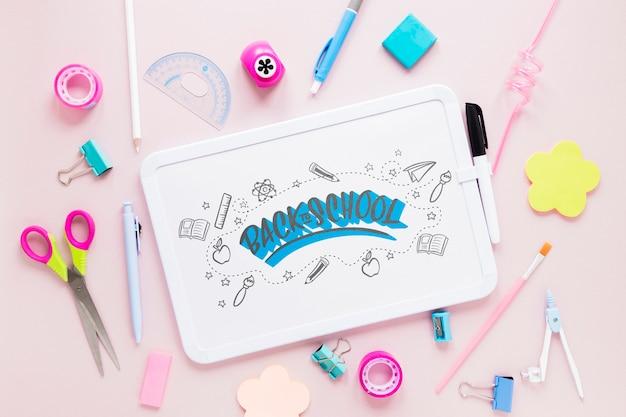 Material escolar com quadro branco em fundo rosa