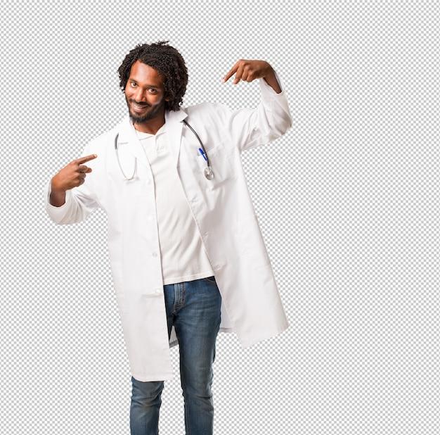Médico americano africano bonito orgulhoso e confiante, apontando os dedos
