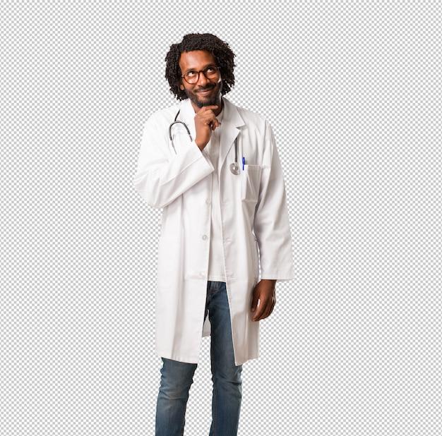 Médico americano africano bonito pensando e olhando para cima, confuso sobre uma idéia, estaria tentando encontrar uma solução