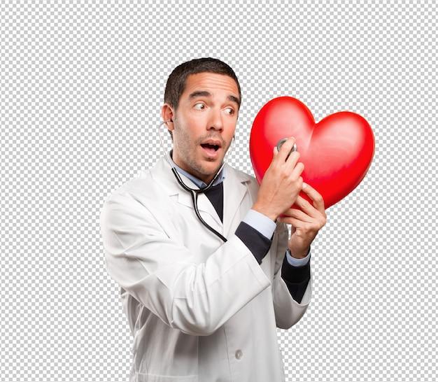 Médico confiante usando um estetoscópio contra fundo branco