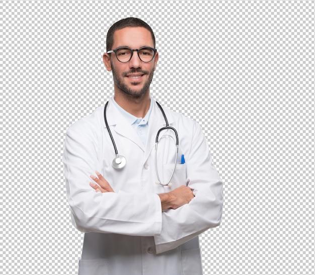 Médico jovem confiante com gesto de braços cruzados